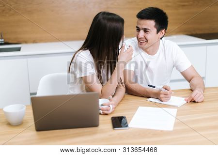 Portrait Of Happy Smiling Young Man And Woman Sitting On Light Background Looking At Each Other. Luc