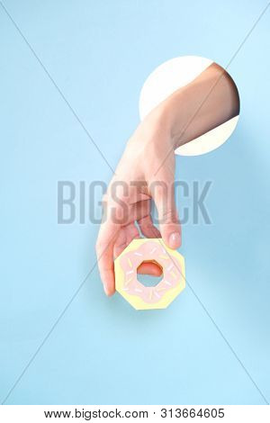 Human Hand Protruding Through Hole In Blue Background, Holding Donut.