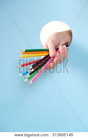 Human Hand Protruding Through Hole In Blue Background, Holding Colored Pencil.