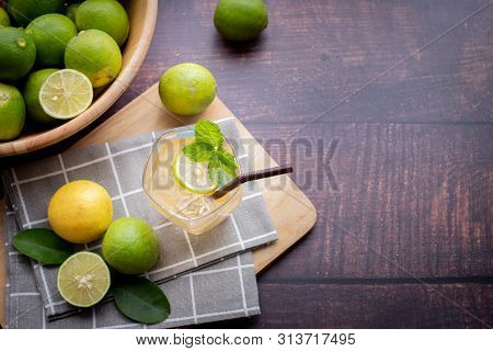 Wood Table With Freshly Squeezed Lemon Juice With Mint And Sliced Lemon, View On Top.