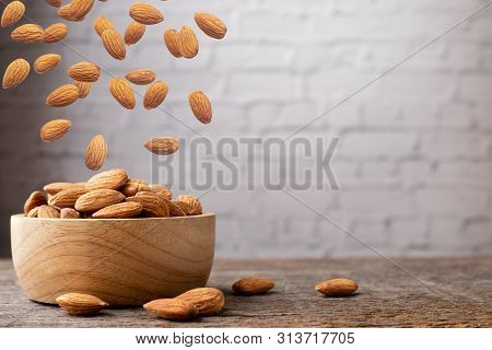 Wood Table With Almonds And Falling Almonds, Front View.