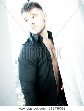 Portrait Of Good Looking Man Standing In Window Behind Curtain