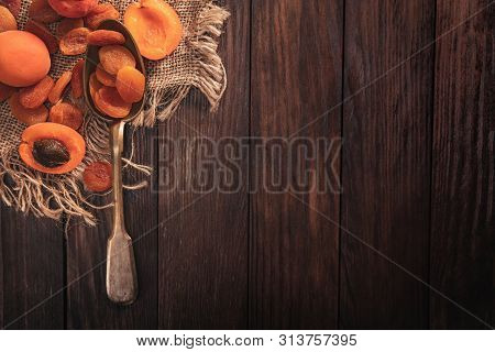 Dried Apricots Arranged On A Fabric And Spoon. Composition In The Old Style With A View From The Top