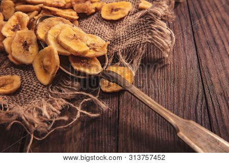 Dried Bananas Stacked On A Fabric And Spoon Over Old Brown Table. Composition In The Old Style