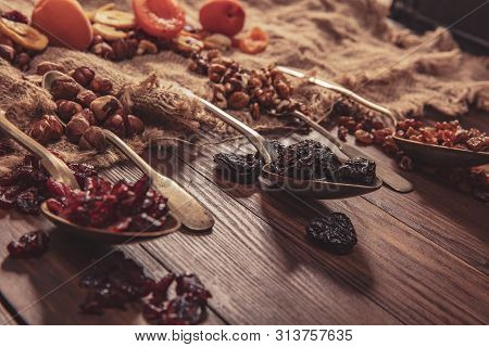 Dried Fruits And Nuts Arranged On A Spoon, Fabric And An Old Table. Composition In The Old Style