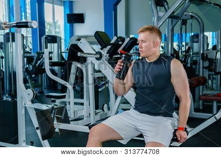 Athlete Drinking From A Shaker Botle For Sports Nutrition In The Background Of The Gym