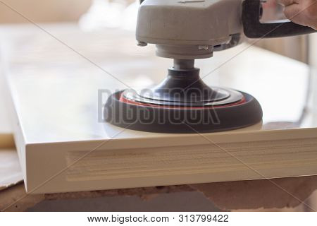 A carpenter polishes the surface of the facade before assembling furniture on a blurred background carpentry workshop, selective focus poster