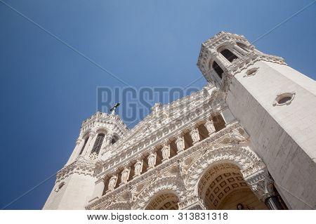 Main Facade Of Basilique Notre Dame De Fourviere Basilica Church In Lyon, France, During A Sunny Aft