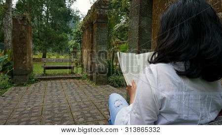 Girl Sit Bench Relaxing With Book In The Garden. Green Nature And Natural Old Stones Walls Backgroun