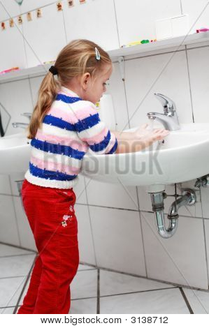 Small girl washing her hands in the bathroom poster