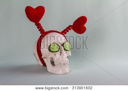Amusing Droll Skull With Two Red Hearts And Two Cucumbers On The Soft Turquoise Background.