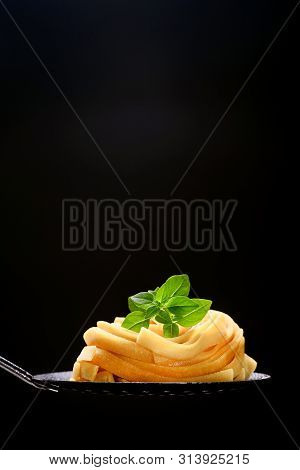 Fettuccine Homemade Uncooked Pasta. Yellow Color Of The Product On A Black Background. Portion On Th