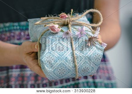 Hands Holding Gift Box With Flowers. Gift Present. Close Up Of Hands Holding Gift Box With Natural T