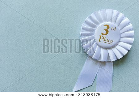3rd Place White Ribbon Rosette With Gold Text For A Competition Runner Up Winner On Blue With Copy S
