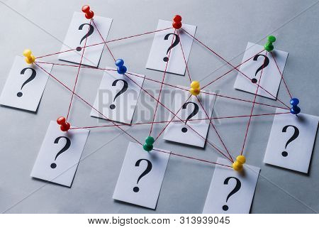 Network Of Printed Question Marks On White Cards Pinned With Thumb Tacks And Joined By String In A C