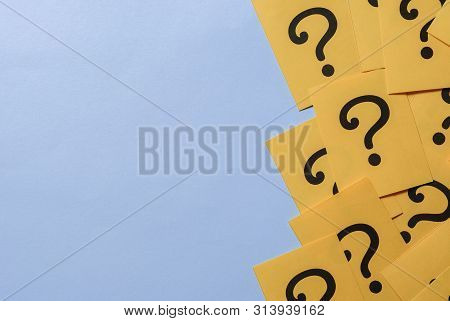 Printed Question Marks On Yellow Paper Or Card Forming A Right Side Border Over A Blue Background Wi