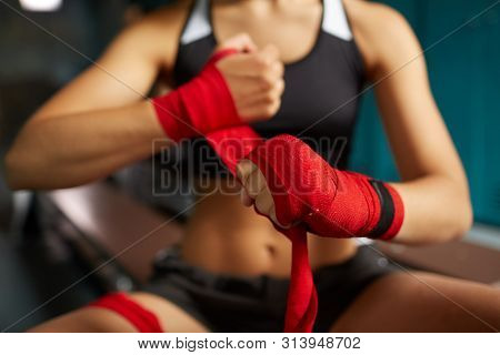 Close Up Of Tough Young Woman Putting On Red Hand Wraps Preparing For Boxing Practice In Sports Club