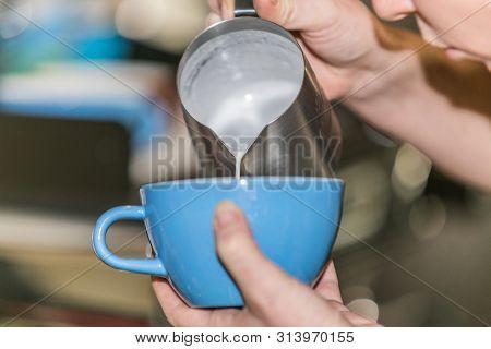 Closeup barista in preparing proper cappuccino pouring milk froth in a cup poster