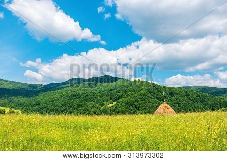 Beautiful Rural Area In Summertime. Haystack On The Grassy Meadow In Mountains. Fluffy Clouds On The