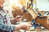 Senior carpenter glueing wooden craft surface and joining with clamps. Woodwork carpenter with equipment and tools at workshop. Handmade diy furniture.Wood part glue joiner poster