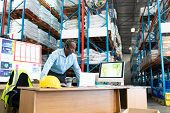 Front view of mature African-american male supervisor working on laptop at desk in warehouse. This is a freight transportation and distribution warehouse. Industrial and industrial workers concept poster