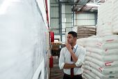 Front view of handsome young mixed-race male supervisor looking at inventory records on wall. This is a freight transportation and distribution warehouse. Industrial and industrial workers concept poster