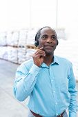 Portrait close-up of handsome mature African-american male supervisor talking on headset in warehouse. This is a freight transportation and distribution warehouse. Industrial and industrial workers poster