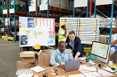 Front view of mature Caucasian female manager and African-american male supervisor discussing over laptop at desk in warehouse. This is a freight transportation and distribution warehouse. Industrial poster