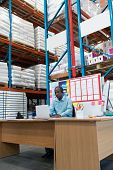 Front view of handsome mature African-american male supervisor working on laptop at desk in warehouse. This is a freight transportation and distribution warehouse. Industrial and industrial workers poster