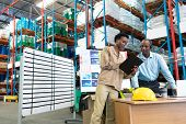Front view of mature African-american male supervisor with beautiful young African-american female coworker discussing over clipboard at desk in warehouse. This is a freight transportation and poster