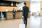 Full length of happy manager awaiting for CEO on business trip arriving at front desk in hotel poster