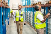 Front view of handsome Caucasian male supervisor walking in warehouse. In front of him an Asian male staff member is writing on clipboard. This is a freight transportation and distribution warehouse. poster