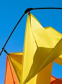 clear blue sky with bright yellow & orange colored fabric kite. rigging, fabric tension & shadow play. poster