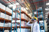 Front view of handsome Caucasian male supervisor using virtual reality headset in warehouse. This is a freight transportation and distribution warehouse. Industrial and industrial workers concept poster