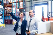 Front view of beautiful mature Caucasian female manager standing with Caucasian male supervisor and pointing at distance in warehouse. This is a freight transportation and distribution warehouse. poster