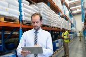 Front view of mature Caucasian male supervisor working on digital tablet in warehouse. This is a freight transportation and distribution warehouse. Industrial and industrial workers concept poster