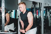 young man trains the muscles of the shoulder girdle using a cable weight machine in the gym poster