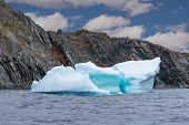 Iceberg floating in the ocean off the coast of Newfoundland, Canada poster