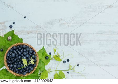 Heap Of Fresh Blueberries And Leaves In A Basket On White Wooden Background. Healthy Eating And Diet