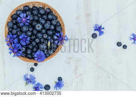 Heap Of Fresh Blueberries And Blue Flowers In A Basket On White Wooden Background. Healthy Eating An