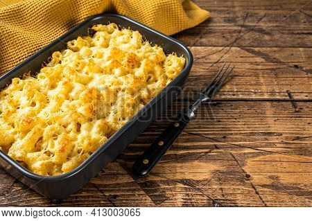 Baked Mac And Cheese American Dish With Cheddar Sauce. Wooden Background. Top View. Copy Space