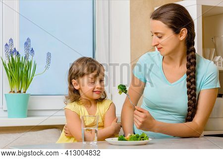 The Child Is Skeptical About Broccoli And Does Not Want To Eat It. Organic Cabbage And Food On A Pla