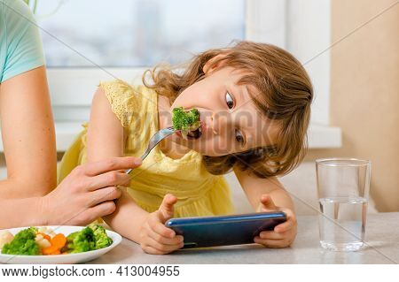 The Problem Is To Distract The Child From The Phone And Feed It With Broccoli. Organic Food And Vege