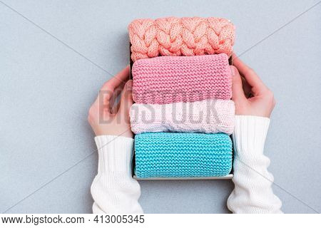 Organization And Order. Women's Hands Hold A Box Of Neatly Folded Knitted Clothes. Top View
