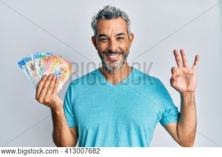 Middle age grey-haired man holding swiss franc banknotes doing ok sign with fingers, smiling friendly gesturing excellent symbol