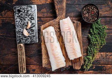 Raw Cod Loin Fillet Steak On Wooden Board With Butcher Cleaver. Dark Wooden Background. Top View