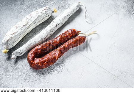 Spanish Salami, Fuet And Chorizo Sausages On A Kitchen Table. White Background. Top View. Copy Space