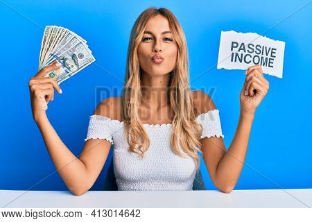 Beautiful blonde young woman holding dollars and passive income text looking at the camera blowing a kiss being lovely and sexy. love expression.