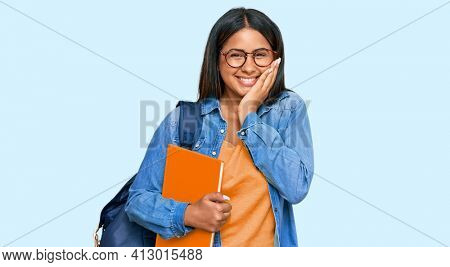 Young latin girl wearing student backpack and holding books laughing and embarrassed giggle covering mouth with hands, gossip and scandal concept