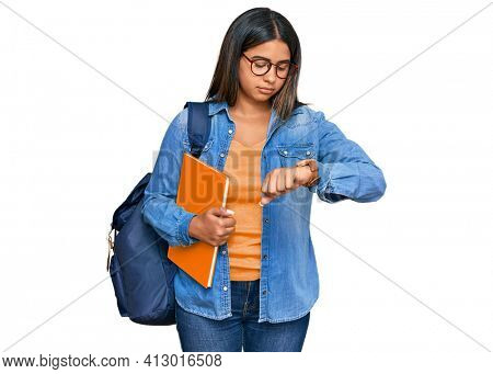 Young latin girl wearing student backpack and holding books checking the time on wrist watch, relaxed and confident